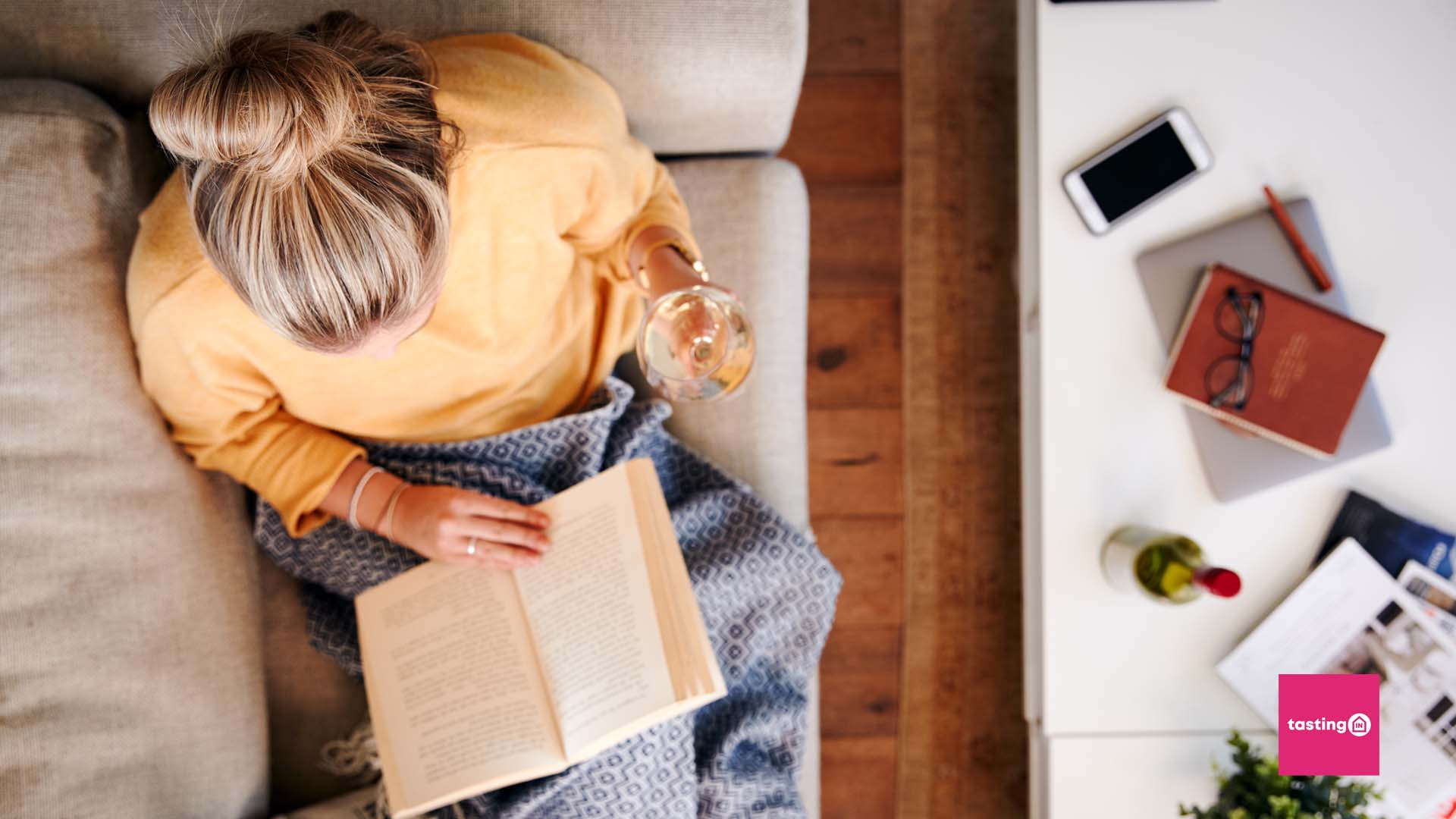 picture of a woman drinking wine and reading a book on the sofa